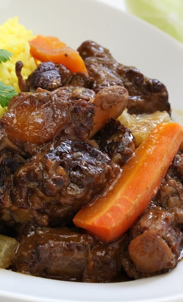 Slow cooker Cuban oxtail stew recipe. Bone-in oxtail with vegetables and spices cooked in a slow cooker and served over the cooked yellow rice. #slowcooker #crockpot #beef #stew #dinner #oxtail