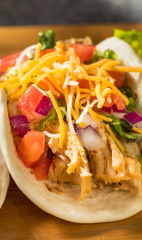 Slow cooker chicken tacos. Puled chicken with taco seasoning cooked in a slow cooker and served on soft tortillas. Yummy recipe! #slowcooker #crockpot #dinner #chicken #tacos #mexican