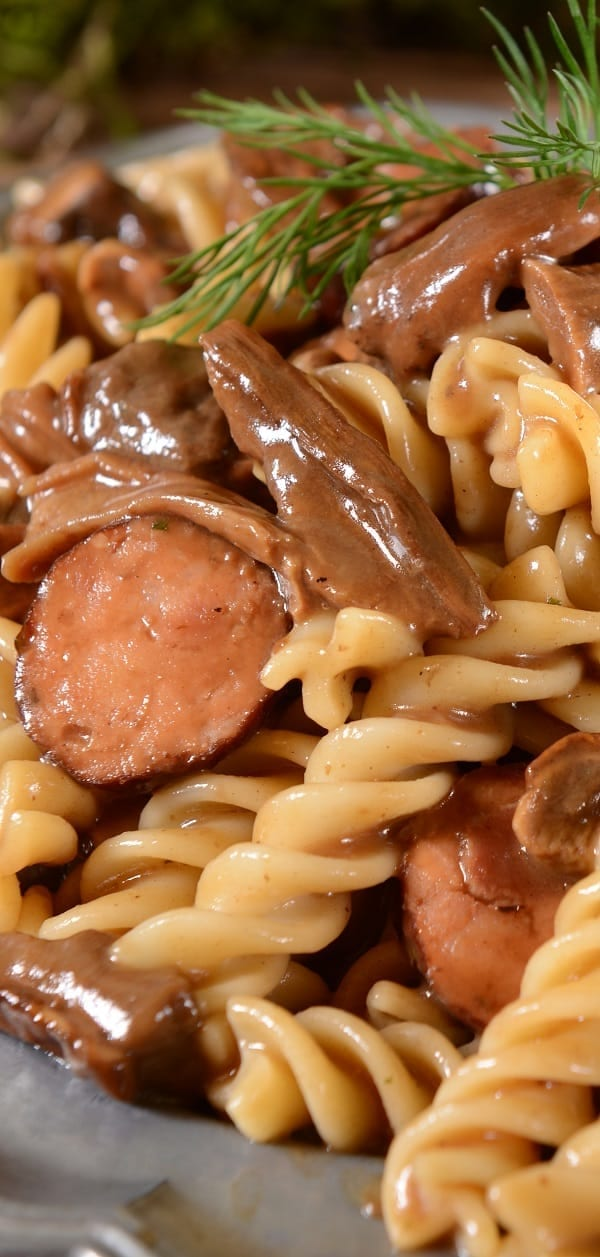 Slow cooker sausage mushroom pasta recipe. Italian sausages with mushrooms and herbs cooked in a slow cooker and served with cooked fusilli pasta. #slowcooker #crockpot #sausage #mushrooms #pasta #dinner